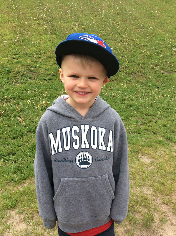 Young child smiling in baseball cap