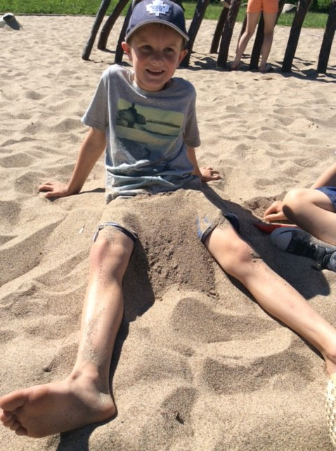 child playing in the sandbox on a sunny day